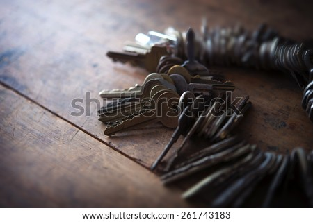 Many old keys placed on a well used old wooden desk with incoming light. Security and encryption, concept image. - stock photo