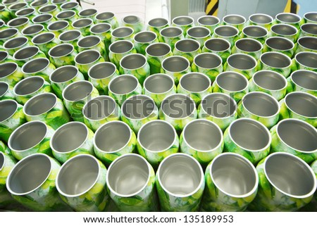 Many open aluminum cans for drinks move on conveyor at modern factory. - stock photo