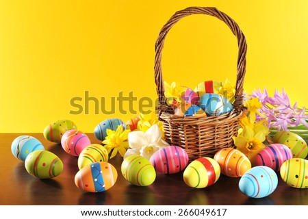 many painted easter eggs with easter basket and hyacinth in front of orange background  - stock photo