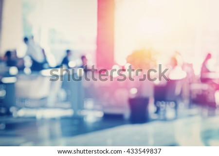 Many people eating in airport cafe. Blurred effect applied. - stock photo