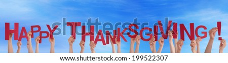 Many People Holding the Words Happy Thanksgiving in the Sky - stock photo