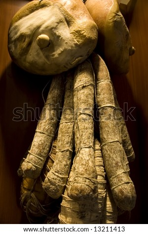 Many pieces of salami and Italian ham (Prosciutto di Parma) hanging in a butchery - stock photo