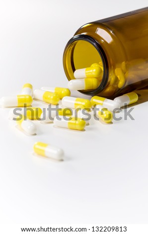 many pills lie on white underground before medication canister - stock photo