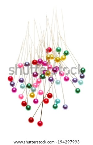 Many pins with colored heads of varying colors lying in a pile. - stock photo