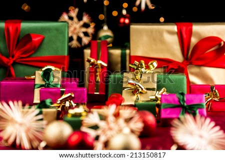 Many plain Christmas presents piled up on a red cloth. All with unicolored bows in red, green and gold. Narrow depth of field resulting in bokeh. Blurred ornaments and stars in front and back. - stock photo