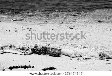 Many plastic and garbage is a pollution on the beach with black and white color,Focus on garbage and blurry on water - stock photo