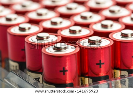 Many red AA batteries in a row - stock photo