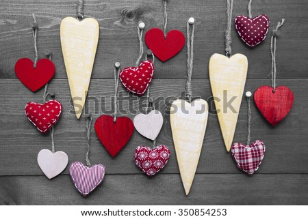 Many Red Hearts Hanging Infront Of Wooden Background. Black And White Image With Colored Hot Spots. Romantic Decoration For Valentines Day. Rustic, Retro Or Vintage Style - stock photo