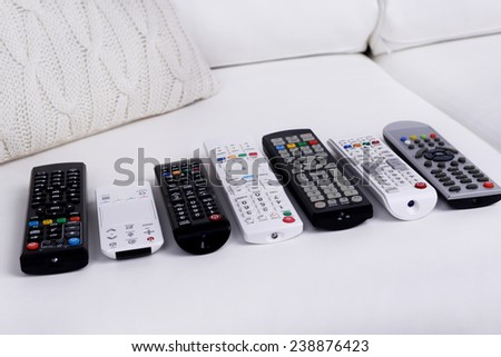 Many remote control devices on sofa - stock photo