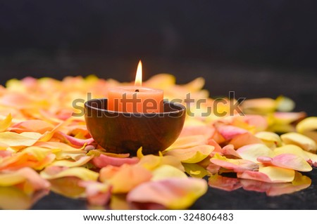 many rose petals with candle in wooden bowl  - stock photo