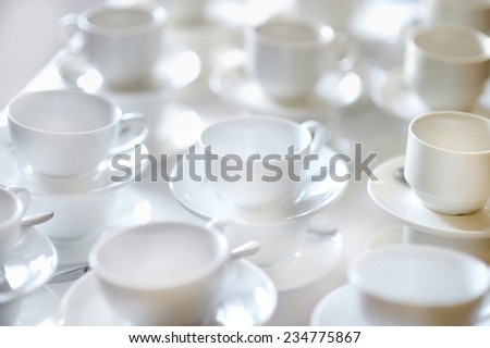 Many rows of pure white coffee cups and saucers - stock photo
