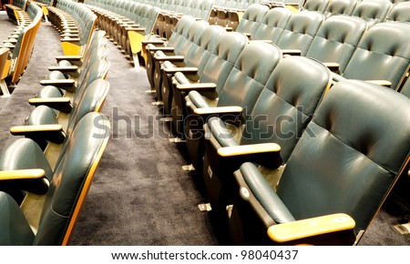 Many rows of wooden chairs at the empty theatre - stock photo