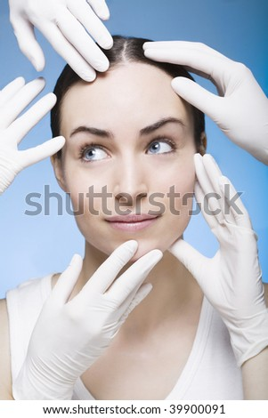 many rubber gloves touching the face of a woman - stock photo