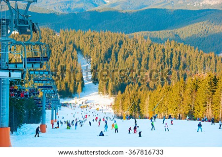 Many skiers and snowboarders on a mountain slope at ski resort - stock photo