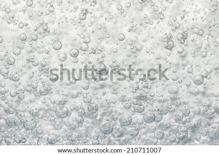 Many small air bubbles flows in a glass of water - stock photo