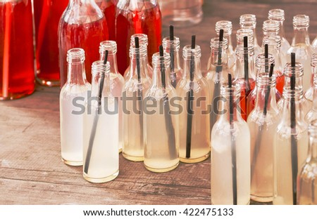Many small bottles with a refreshing vitamin drinks on a wooden table in a outdoor cafe. Still-life with energy cocktails and black tubes inside  - stock photo