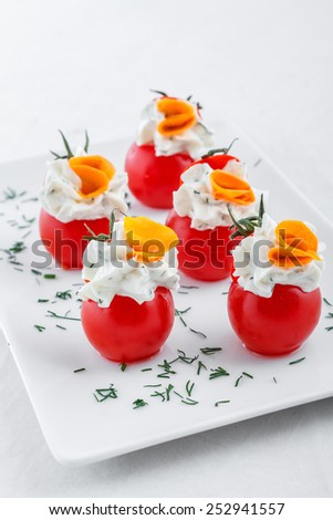 Many small tomatoes stuffed with cream cheese - stock photo