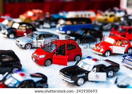 Many small toy cars lined up on the beautiful white fabric. - stock photo