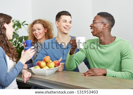 Many smiling colleagues drinking coffee in break room - stock photo