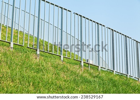 Many steel guards with green grass and blue sky - stock photo