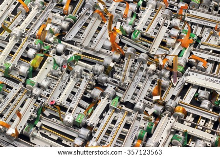 Many stepper motors from floppy and cd dvd drives. Industrial electronics waste as background. - stock photo