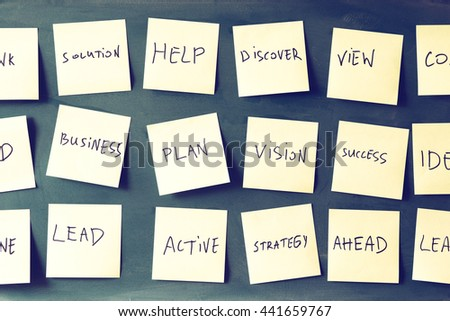 many sticky notes attached to blackboards with handwriting text. retro filtered - stock photo