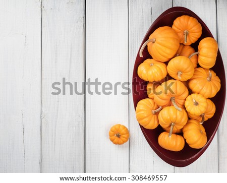 Many Thanksgiving, Colorful Fall Mini Pumpkins in a Wood Bowl on Rustic White or gray Painted Board Background with room or space for copy, text, your words.  Above view horizontal with bowl on side  - stock photo