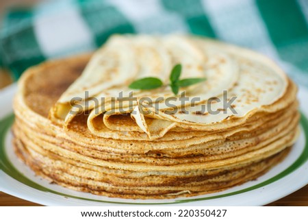 many thin pancakes on a plate on a wooden table - stock photo