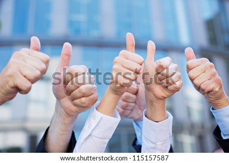 Many thumbs of different business people pointing up - stock photo