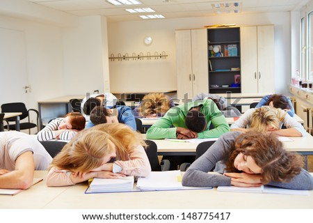Many tired students sleeping in classroom with their heads on the table - stock photo