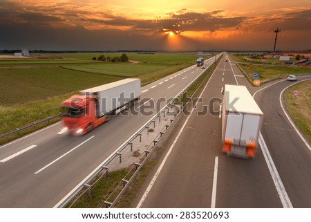 Many trucks in motion blur on the freeway towards the setting sun. Rush hour on the motorway near Belgrade - Serbia. - stock photo