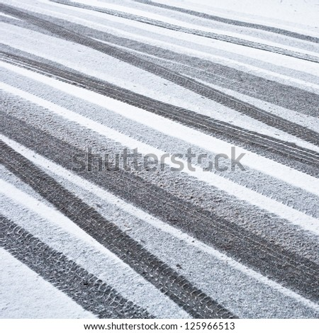 Many tyre tracks on a road  in the snow - stock photo
