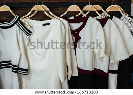 Many white blouses on hangers in the dressing room. - stock photo