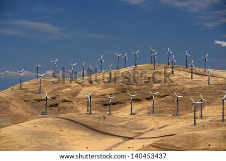 many wind power generator on grass hills - stock photo