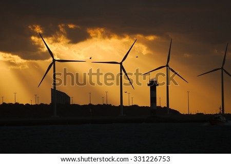Many wind power turbines in twilight - stock photo