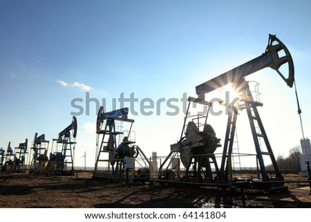 many working oil pumps silhouette in row against sun - stock photo