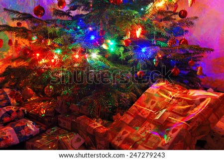 Many wrapped presents under a lit Christmas tree - stock photo