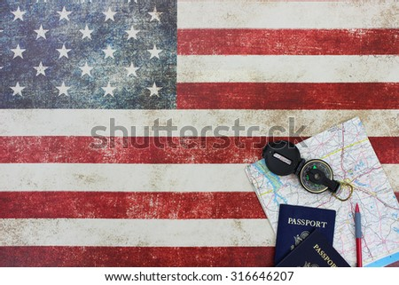 Map, compass and passports on vintage American flag canvas background - stock photo