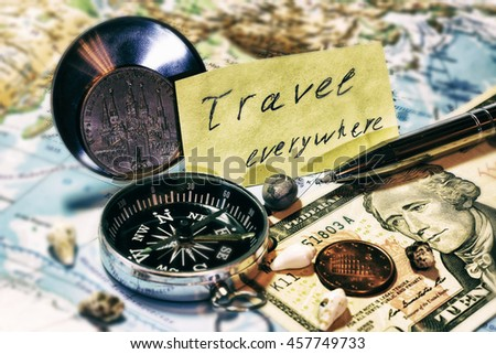 "Map of the world with metallic compass, pen, coins and inscription ""Travel everywhere"" - stock photo"
