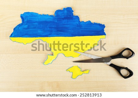 Map of Ukraine and scissors - concept of disintegration of the country - stock photo