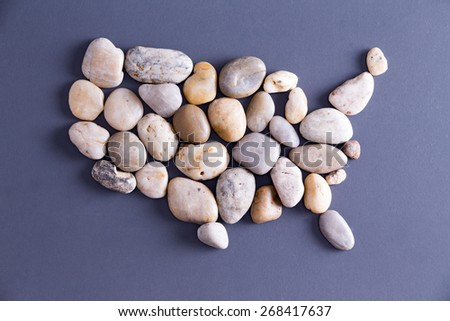 Map of United States of America, made of white and beige pebbles, concept of political power and stability, with copy space on blue - stock photo