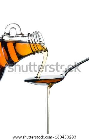 maple syrup pourin on spoon on white background - stock photo