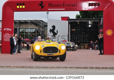 MARANELLO (MO) ITALY - MAY 18: Yellow Ferrari 225 S Vignale spider, built in 1952, exits the Ferrari Museum during the 1000 Miglia historic car race, on May 18, 2013 in Maranello (MO) - stock photo