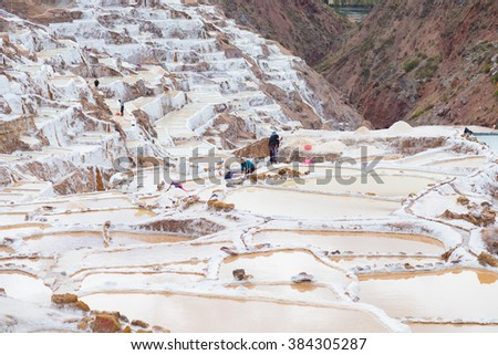 Maras, Peru - September 5, 2015: Workers, mostly women and girls, manually extracting minerals from terraced salt pans in Maras, Urubamba Valley, Peru. Concept of manual work in developing countries. - stock photo