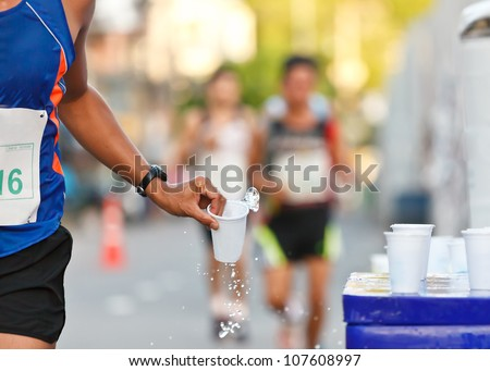 Marathon runner picking up water at service point - stock photo