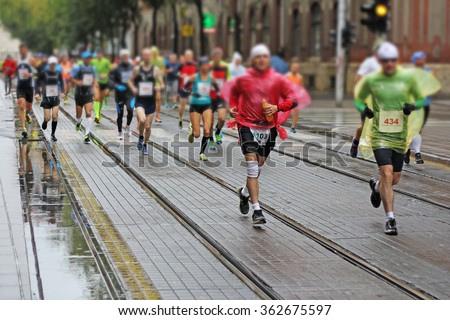Marathon runners race in city streets, blurred motion - stock photo