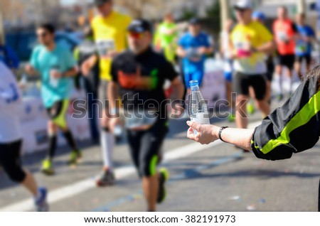 Marathon running race, runners on road, volunteer giving water on refreshment point  - stock photo