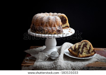 Marble bundt cake on wooden table, black background - stock photo