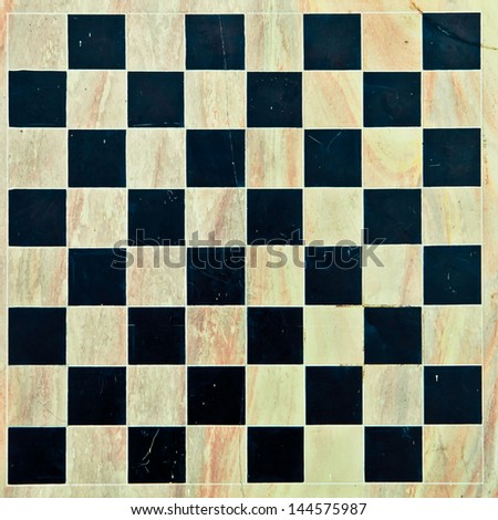 Marble chessboard as a detailed background in subtle vintage tones - stock photo