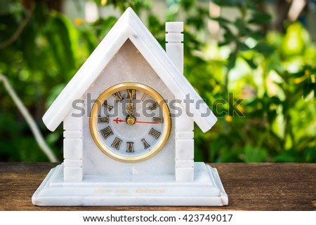Marble clock on wooden background at 12.00 O's clock - stock photo